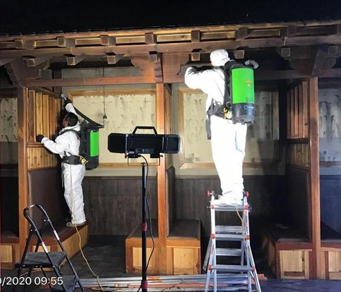 SERVPRO technicians dressed in PPE Removing Black Soot from Walls and Ceilings with Chemical Sponge