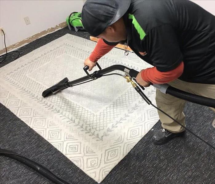 SERVPRO Technician extracting standing water from white Carpet